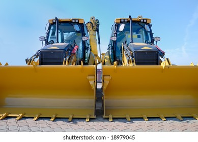 Two new bulldozers on a showcase .