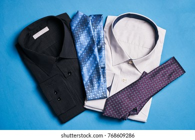 Two new colorful shirts with ties for men, on blue background, top view. Men's fashion