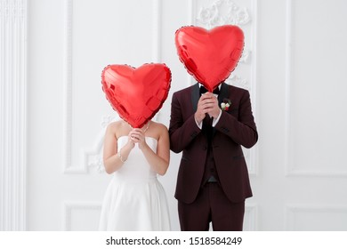 Two newlyweds cover their faces with heart-shaped balloons