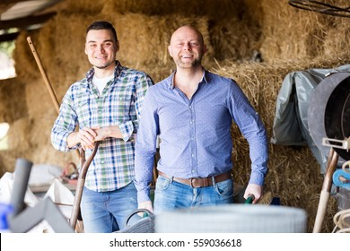 Two nice farm workers tedding the hay at hayloft. Focus on the right man