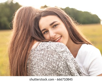 Two nice females are hugging on the field. Best friends