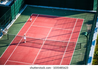 Two noname children play on tennis court outdoor