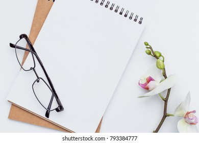 Two notebooks lying on a white table With glasses, office concept