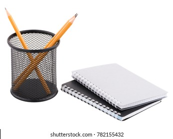 Two notepad and next to container with sharp pencils inside. Isolated on white background.