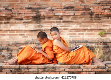 Two novice reading and studying blackboard with funny in old temple at sunset time, Ayutthaya Province, Thailand
