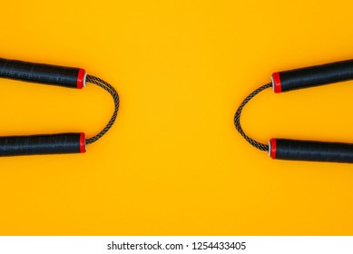 Two nunchats on a yellow background, flat lay. Nunchaku for training