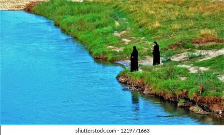 Two nuns fishing. 27.Aug.2010 two nuns fishing in Voronet village - Romania