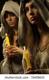 Two nuns praing with candles in their hands