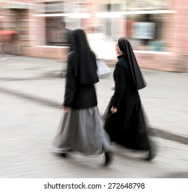 Two nuns walking in motion blur. Intentional motion blur