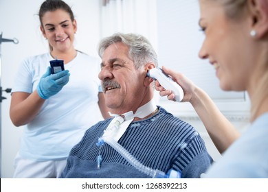 Two nurses care for an intensely awake patient in the hospital nursing home