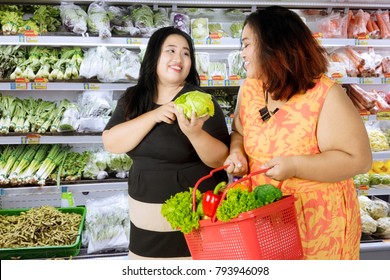 Two obese women buying organic vegetables and holding a shopping cart in the grocery store