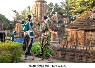 Two odissi dancers striking a pose in front of Mukteshvara Temple,Bhubaneswar, Odisha, India