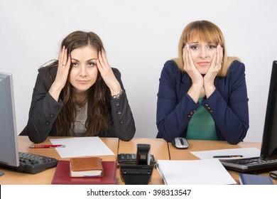 Two office employee sitting with depressed and frightened look