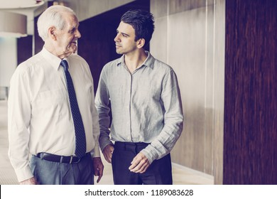 Two office employee walking along office space. Junior employee listening to senior mentor in white shirt and tie. Business meeting and coaching concept