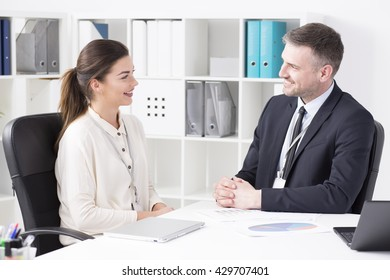 Two office wokers discussing, sitting beside desk in light office