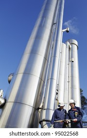 two oil and gas workers with large shiney gas and fuel pipelines
