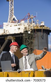 Two oil platform inspectors with a laptop, with the platform in the background