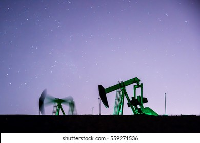 Two oil pump jack silhouettes backlit by city lights & stars