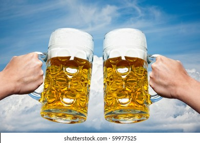 Two Oktoberfest beers on a Bavarian blue sky background and white clouds.