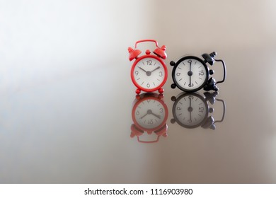 two old alarm clocks red and black near showing time alarm clock background time is running the black one fell down broken wrong time