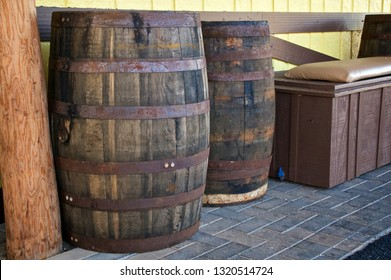 Two old antique wooden wine casks or beer barrels are outside against a wall.