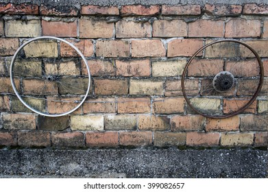 Two old bicycle wheels on a brick wall