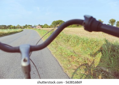 Two old bikes on journeys with human shadow on the road and green field.