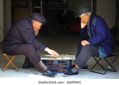 Two old Chinese man play Xiangqi. Xiangqi, or Chinese Chess, is an extremely popular game in China.
