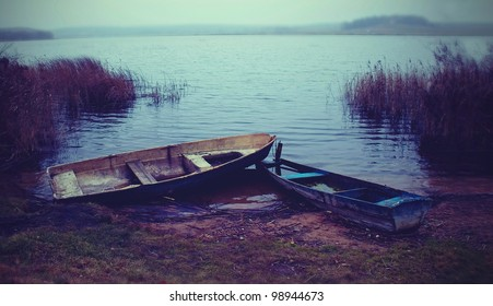 two old dilapidated boat on the lake in autumn