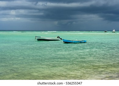 Two old fishing boats in clear sea with a stormy background