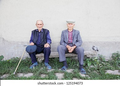 Two old friends sitting on bench at wall outdoors with chicken aside