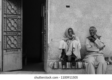 Two old friends sitting together chatting and smiling in a Nubian village in Aswan, Egypt. February 2017