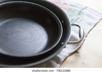 Two old frying pans stacked together on a wooden background.
