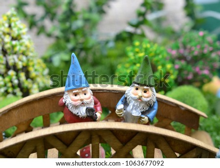 Two Old Garden Gnomes On Wooden Bridge In Enchanted Garden With Flowering  Trees