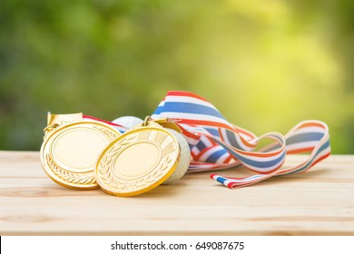 two old gold medal and golf ball on wood in morning, soft background, Winner concept