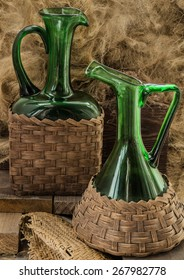 Two old green wine bottles on wood background hay