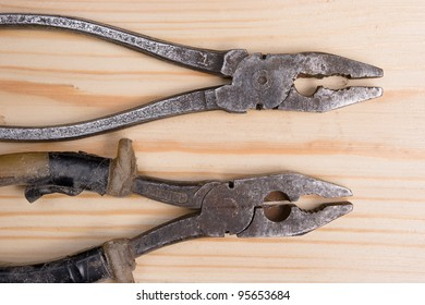two old hardly used pliers on wooden surface
