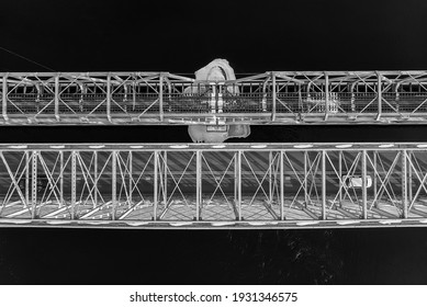 Two old iron bridges crossing the river. The steel structures are covered in frost and the small island below them has a snow cover.