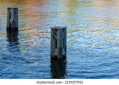 two old iron columns of a support closeup in river water