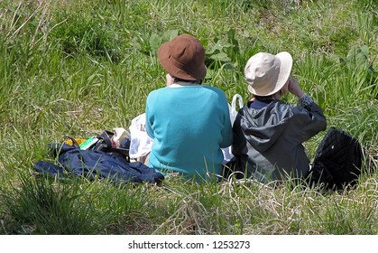 """Two old Japanese women friends in the grass,wearing the very specific """"Japanese hiking hats""""."""