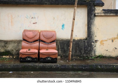 Two old leather chairs near grungy wall on the footpath