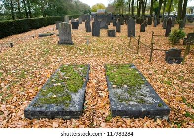 Two old lying gravestones on a graveyard in the autumn