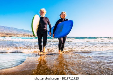 two old and mature people having fun and enjoying their vacations outdoors at the beach wearing wetsuits and holding a surfboard to go surfing in the water with waves - active senior smiling
