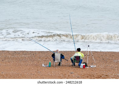 Two old men on a beach fishing - a relaxing way to pass the time in retirement; Kent, England.