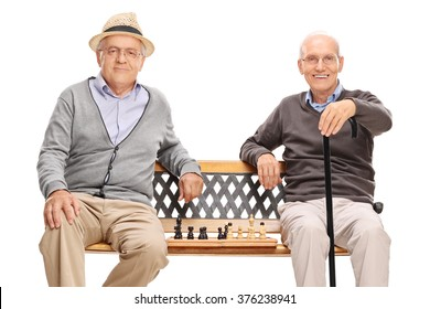 Two old men posing sitting on a wooden bench with a chessboard between them isolated on white background