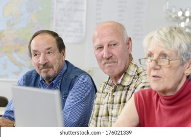 Two old men and a woman with a laptop in front of her.
