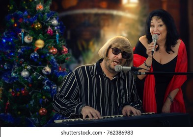 Two old musicians perform popular Christmas songs. Man in light yellow wig plays electric organ. Black haired woman in big red scarf is singing next. Decorated christmas tree stands in left side