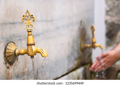 Two old public taps in Istanbul, Turkey. Water flowing and person washing hands in background.