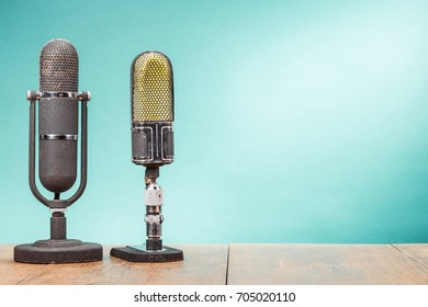 Two old retro big microphones from 50s on table front gradient mint green background. Vintage style filtered photo