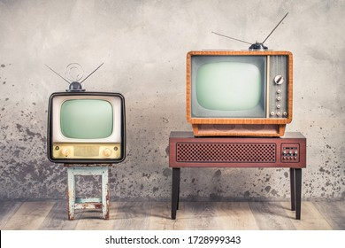 Two old retro classic analog CRT TV set receivers and aged wooden television stand with outdated amplifier front aged concrete wall background. Broadcasting, news concept. Vintage style filtered photo